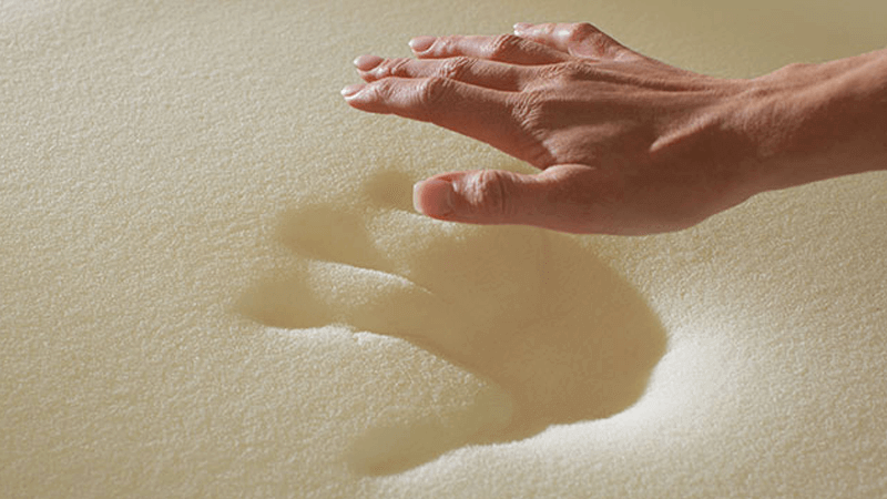 Hand pressing into memory foam mattress